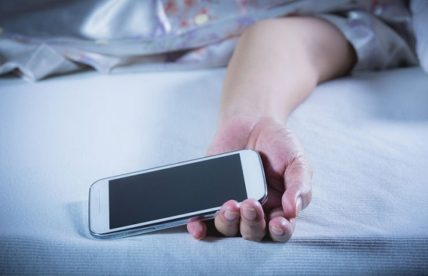 Ένας στους δύο είναι αγκαλιά στο κρεβάτι με το κινητό